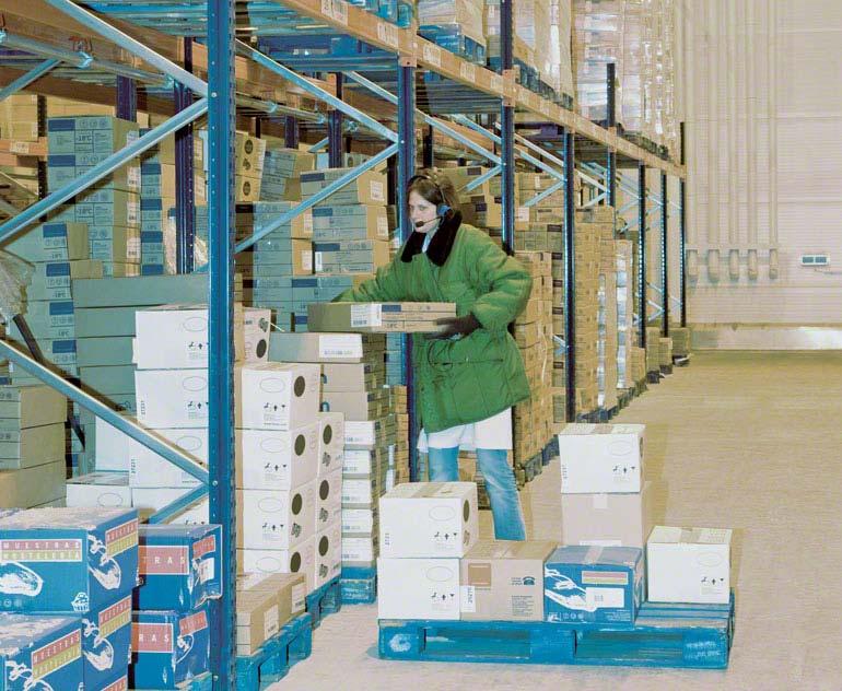 Orderpicking op vloerniveau in een magazijn met palletstellingen