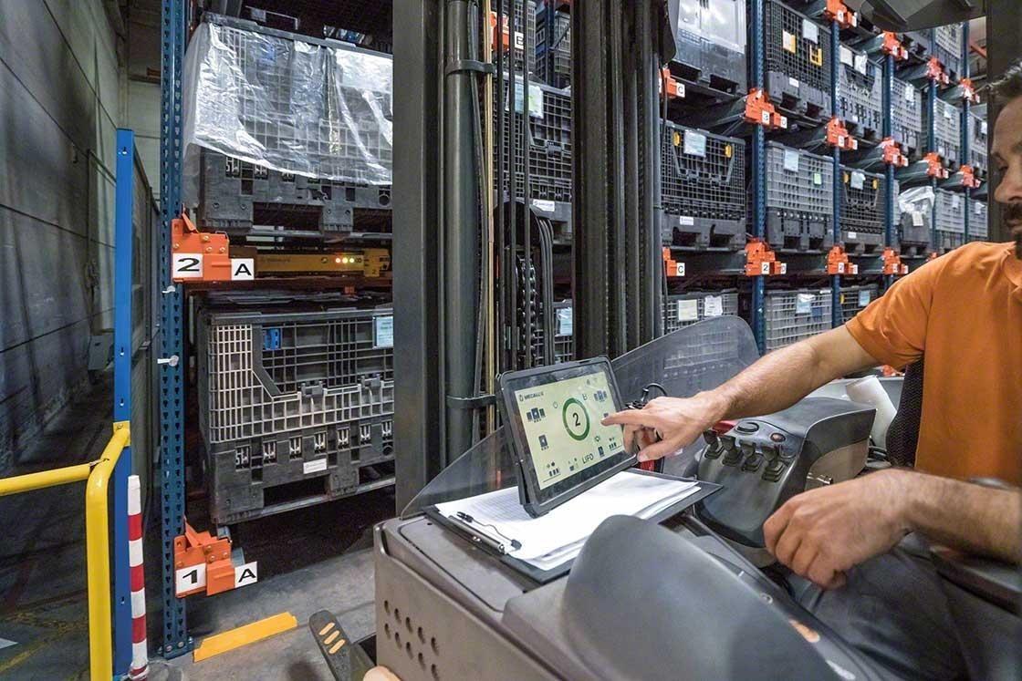 Vanaf de heftruck stuurt een magazijnmedewerker de Pallet Shuttle aan met behulp van een tablet