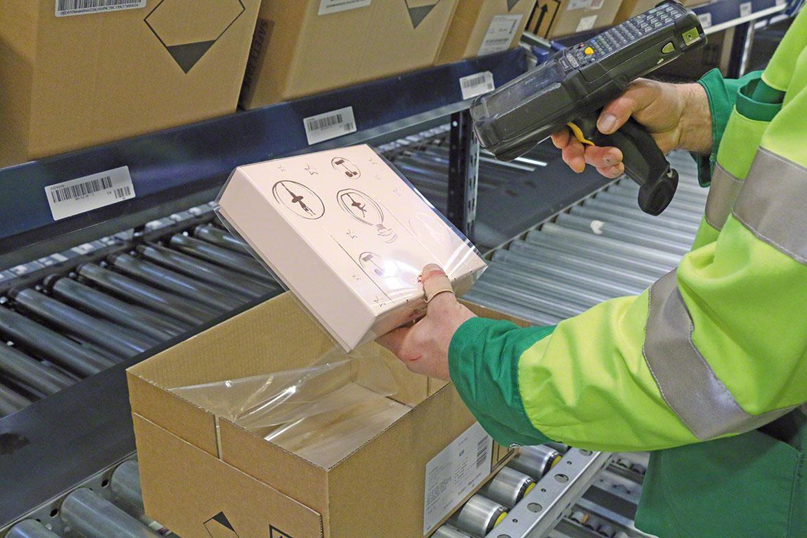 Magazijnmedewerker zet een artikel klaar met behulp van een Rf scanner die verbonden is aan de orderpicking software